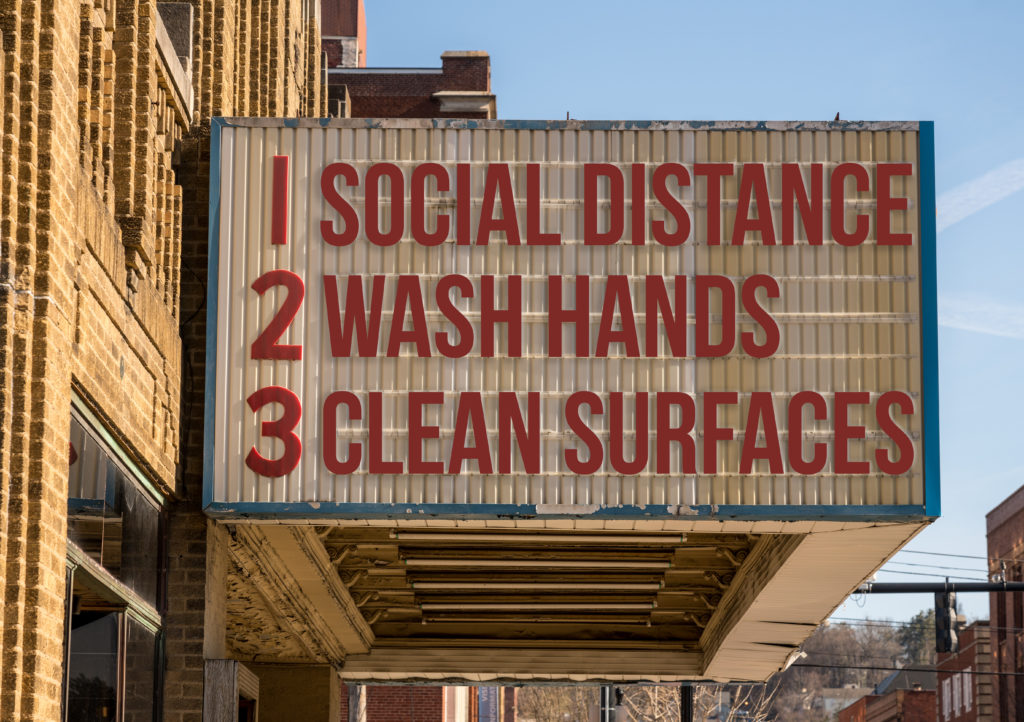 Movie marquee with COVID-19 notices to social distance, wash hands, and clean surfaces